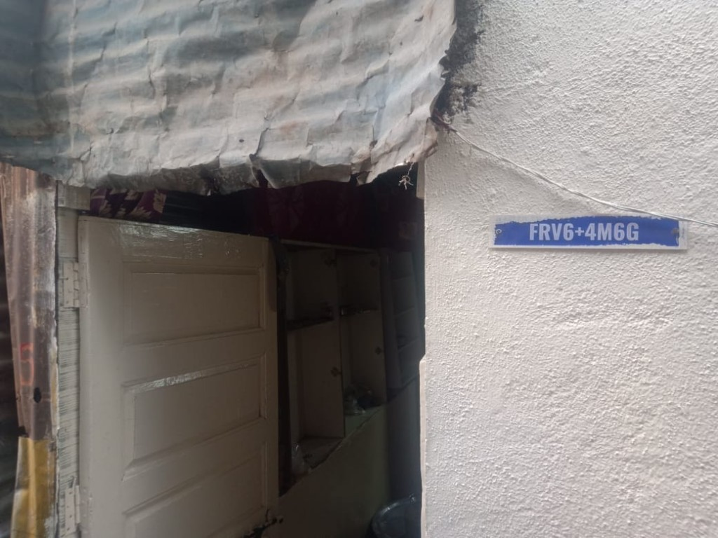 Plus Code plate installed at the beneficiary's home entrance